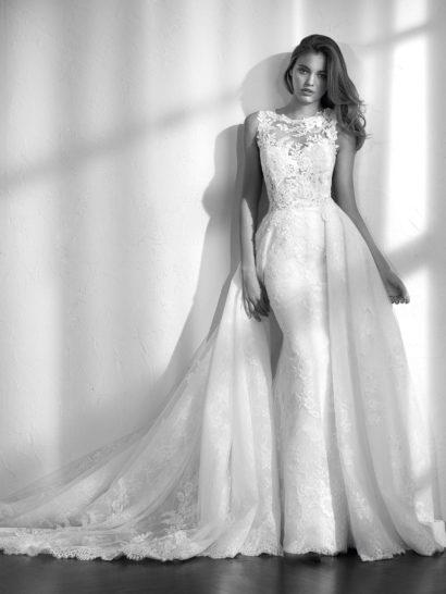 Это особенное свадебное платье, в основе образа – силуэт «русалка» с вырезом «лодочкой» и полупрозрачной спинкой, оформленной тюлем и кружевом с вышивкой.  Дополнить его можно пышной верхней юбкой, созданной из нескольких слоев тюля с кружевом и вышивкой.  Акцент в силуэте верхняя юбка делает на стройной талии.