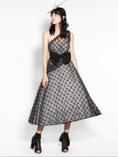 Необычное вечернее платье А-силуэта притягивает внимание сияющей отделкой и асимметричным кроем верха. На линии талии – широкий эксцентричный пояс, украшенный спереди крупным бантом.  Лиф с вырезом в форме сердечка дополнен полупрозрачной бретелью. Тонкая ткань с мелким рисунком и блестящей вышивкой покрывает платье по всей длине, наполняя образ оригинальностью.
