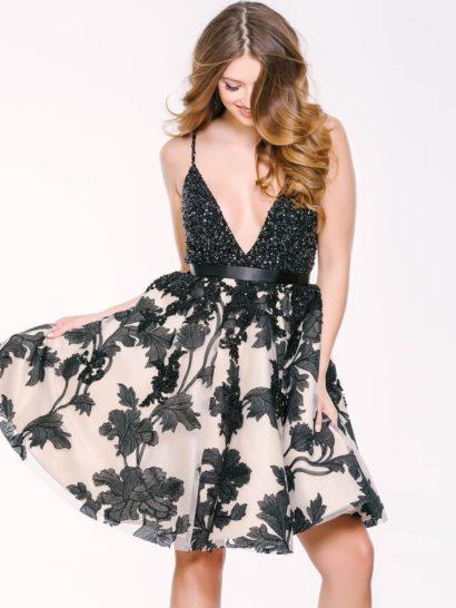 Кокетливое вечернее платье с пышной юбкой длиной чуть выше колена. Особенное внимание привлекает лиф с глубоким V-образным вырезом – он полностью покрыт слоем бисерной отделки. От талии, выделенной лаконичным черным поясом, спускается розовая юбка, декорированная контрастными черными аппликациями. Их цветочный рисунок поддерживает романтичный характер наряда.