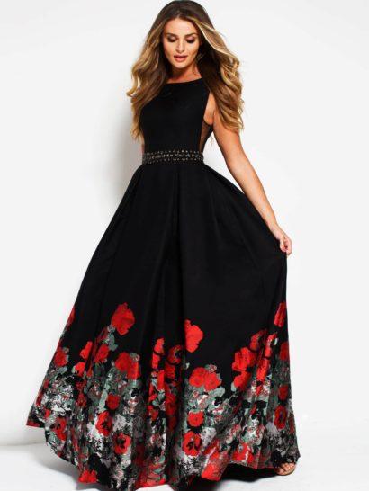 Черное вечернее платье создает эффектный и выразительный образ. Элегантная юбка в пол декорирована по низу подола цветочным узором в алых тонах. Закрытый лиф с вырезом «бато» дополнен разрезами с полупрозрачными вставками по бокам. Сзади платье украшает женственное округлое декольте. Заключительным штрихом служит сияющий пояс на талии.