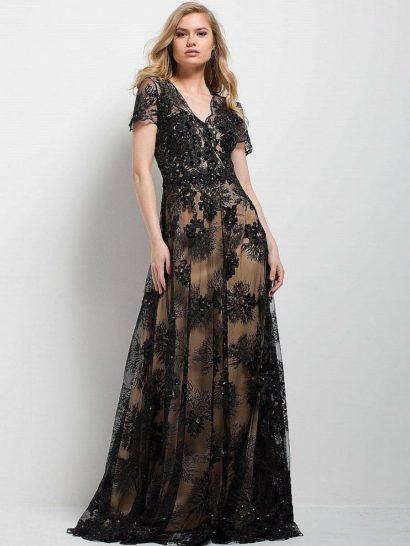 Прямое вечернее платье с юбкой в пол впечатляет элегантной красотой. Бежевая подкладка служит гармоничным дополнением тонкого кружевного верха черного цвета, покрывающего платье по всей длине. Изящный V-образный вырез красиво смотрится в сочетании с коротким рукавом из полупрозрачной ткани. Спинка вечернего платья полностью закрыта.