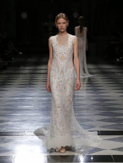 Впечатляющее свадебное платье с эффектом кружевной татуировки на обнаженной коже. Обеспечивают его прямой силуэт, отделка белым кружевом шантильи и вышивка на тюле, располагающемся на бежевой подкладке.  Кажется, что нежный ажурный узор изображен прямо на коже невесты, что наполняет образ невероятной женственностью.
