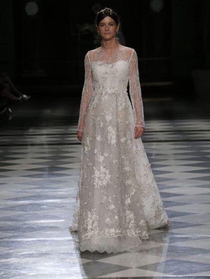 Свадебное платье с длинным полупрозрачным рукавом просто излучает романтичность и женственность. Белоснежная ткань прекрасно дополнена сиянием стразов, украшающих лиф и рукава. Легкая юбка из тюля декорирована вышивкой и атласными цветами.