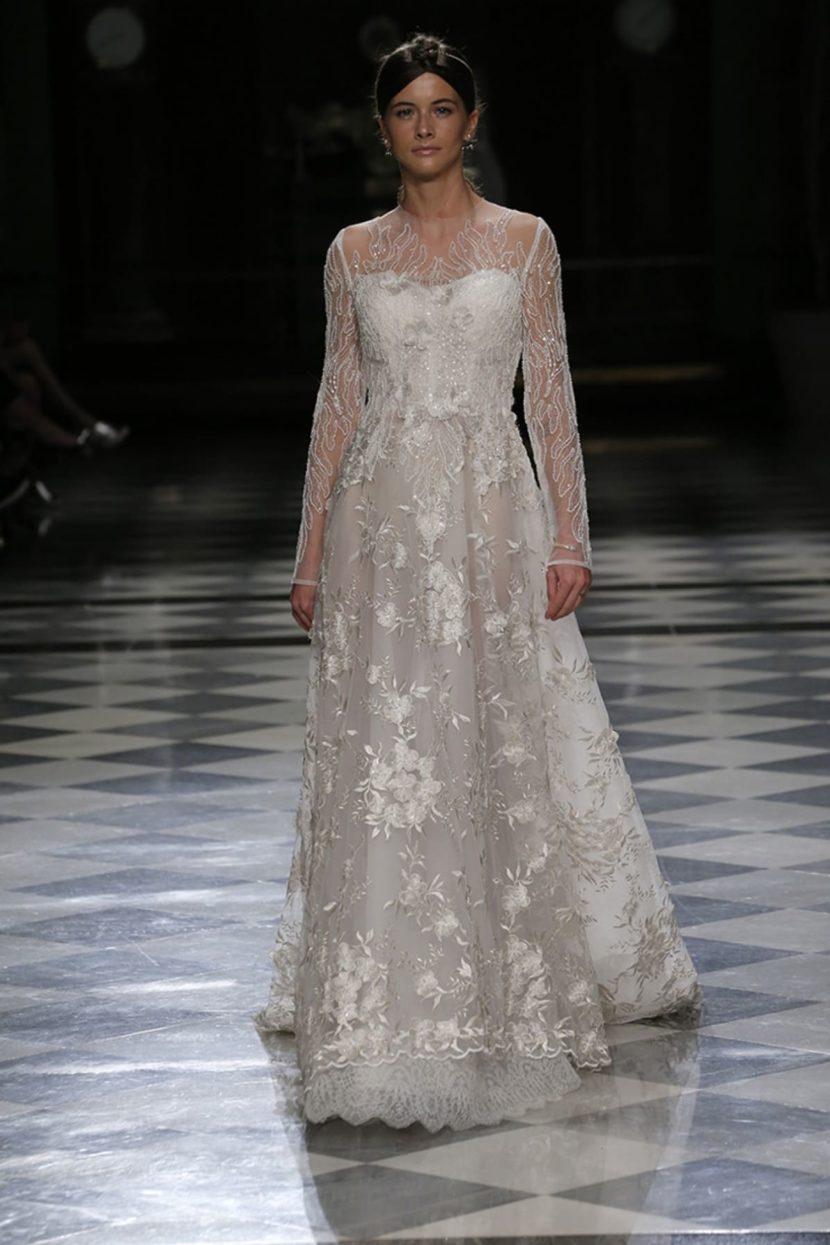 Свадебное платье с длинным рукавом и цветочной вышивкой на юбке.