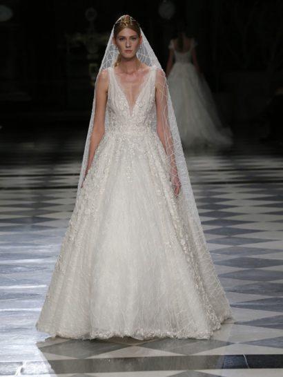 Романтичное настроение и изысканность деталей, характерная для образов высокой моды, являются ключевыми характеристиками этого свадебного платья. Сочетание глубокого V-образного выреза декольте с бальной юбкой, подчеркивающей фигуру и созданной из нескольких слоев органзы с цветочной вышивкой, очаровывает. Этот образ в каждой мелочи подчеркивает женственность невесты.