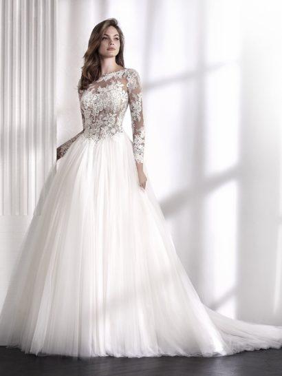 Изысканное свадебное платье создает контрастный образ, будто сложенный из двух элементов. Пышная бальная юбка создана из нескольких слоев тюля. Ее дополняет чувственный верх с иллюзией прозрачности и длинным рукавом. Тонкая ткань декорирована вышивкой и аппликациями. Верх можно преобразить с помощью непрозрачной подкладки.