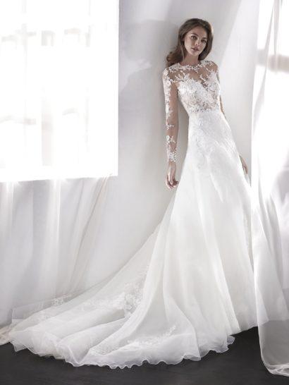 Впечатляющее свадебное платье с юбкой А-силуэта и полупрозрачным верхом с рукавом. Это очень женственный образ, подчеркивающий чувственность обладательницы пышной юбкой и иллюзией обнаженной кожи в области декольте и на спинке. Свадебное платье можно дополнить подкладкой, чтобы корсет не был прозрачным.