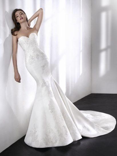 Стильное и сексуальное свадебное платье «русалка» производит неизгладимое впечатление. Изысканный крой без рукавов, воплощенный в атласе с кружевом шантильи, дополнен отделкой – вышивкой нитью и бисером. Узор отделки акцентирует силуэт, подчеркивая изгибы фигуры от юбки до открытого выреза «сердечком.