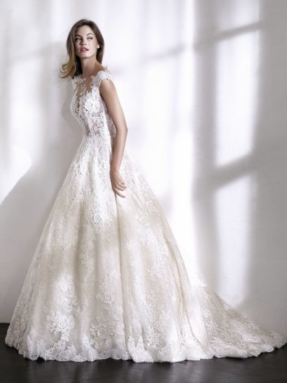 Романтичное свадебное платье с бальным силуэтом и без рукавов, созданное из кружева и тюля, украшенного вышивкой. Чудесный силуэт, акцентирующий талию, дополнен классической объемной юбкой и корсетом с иллюзией прозрачности. Сияющий тюль с деликатной вышивкой скрывает обнаженную кожу – но образ можно сделать и более сдержанным, дополнив его съемной подкладкой к корсету.