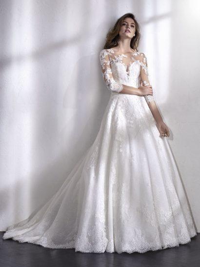 Бальное свадебное платье с невероятно романтичным верхом с иллюзией прозрачности. Оригинальный крой сочетает тонкий тюль, украшенный вышивкой, с аппликацией. Из тюля созданы не только вставки, но и рукава длиной в три четверти. Верх контрастирует с невероятно пышной юбкой, создавая стильный образ для уникальной невесты.