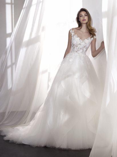 Свадебное платье становится настоящим воплощением любви, сочетая роскошную юбку из тюля с драпировками, полными динамики, и лиф из кружева шантильи с вышивкой и бисером. Платье с V-образным вырезом наполнено женственностью, а контраст тонкой ткани верха и элегантной юбки придает образу индивидуальность. Корсет можно дополнить съемной подкладкой из непрозрачной ткани.