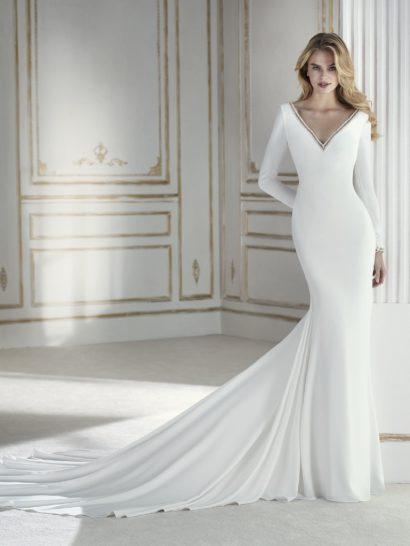 В этом свадебном платье простота становится синонимом красоты, женственности и элегантности. Это удивительный наряд силуэта «русалка», созданный из крепа и дополненный шлейфом. Длинные рукава контрастируют с минималистичным дизайном, очерчивающим декольте V-образным вырезом. Края выреза декорированы бисером и смотрятся чувственно. Это свадебное платье сразу притягивает взгляды.