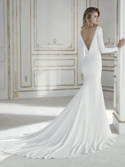Лаконичное свадебное платье с длинным рукавом и V-образным вырезом.