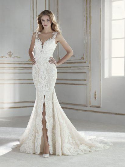 Великолепное свадебное платье силуэта «русалка» декорировано кружевом и тюлем с аппликациями. Это очень женственный образ, подчеркивающий чувственность высоким разрезом по центру подола и V-образными вырезами декольте и на лифе, и на спинке. Оба декольте декорированы кружевом, делающим край фигурным. Это современный и очень романтичный дизайн.