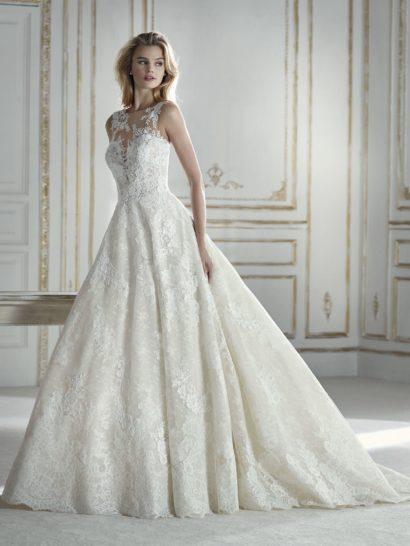Кружево и тюль с вышивкой создают чувственное бальное свадебное платье, подчеркивающее естественную линию талии. Изысканные детали отделки подчеркнуты полупрозрачностью ткани. Особенно притягательно смотрится декольте с иллюзией обнаженной кожи. Кажется, что деликатные цветочные узоры покрывают кожу невесты, а не ткань платья.