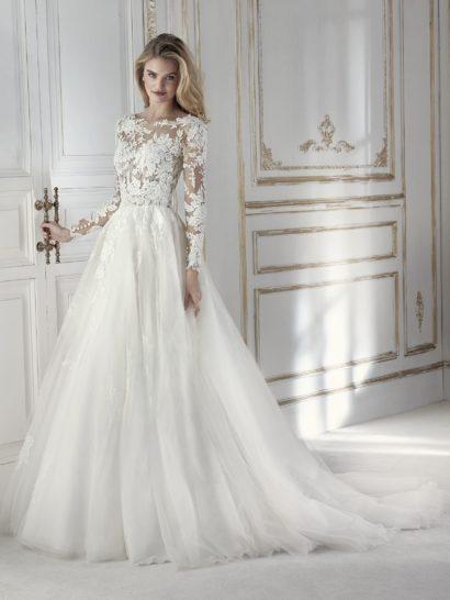 Изысканное свадебное платье с полупрозрачным верхом и юбкой бального силуэта, созданной из тюля. Изящный вырез «лодочкой» красиво сочетается с V-образным декольте на спинке. Тонкие ткани лифа сливаются с кожей, создавая эффект обнаженности. Сделать образ сдержаннее поможет съемная подкладка. Это идеальное платье для особенного дня!