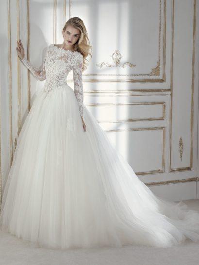 Великолепное бальное свадебное платье подчеркивает естественную линию талии. Юбка из тюля очаровывает объемом и контрастирует с облегающим верхом с вырезом «бато» и длинным рукавом. Украшением верха становится иллюзия прозрачности, подчеркнутая аппликациями, вышивкой и бисерными деталями.
