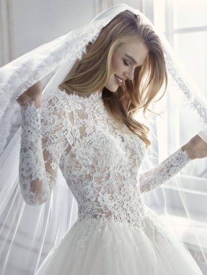 Пышное свадебное платье с вырезом «бато» и изящными рукавами.