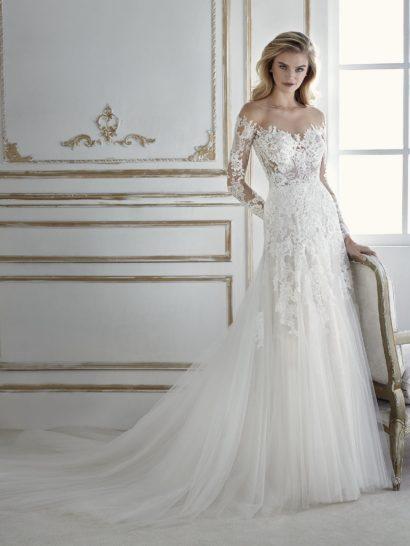 Чудесное свадебное платье с воздушной юбкой. Силуэт с многослойным низом, украшенным кружевными аппликациями, невероятно красив в динамике. Верх облегает фигуру. Лиф с открытыми плечами и длинными рукавами дополнен V-образным вырезом и создан из тонкой полупрозрачной ткани, к которой прилагается съемная подкладка. Это романтичное свадебное платье, которое подчеркнет чувственность обладательницы.