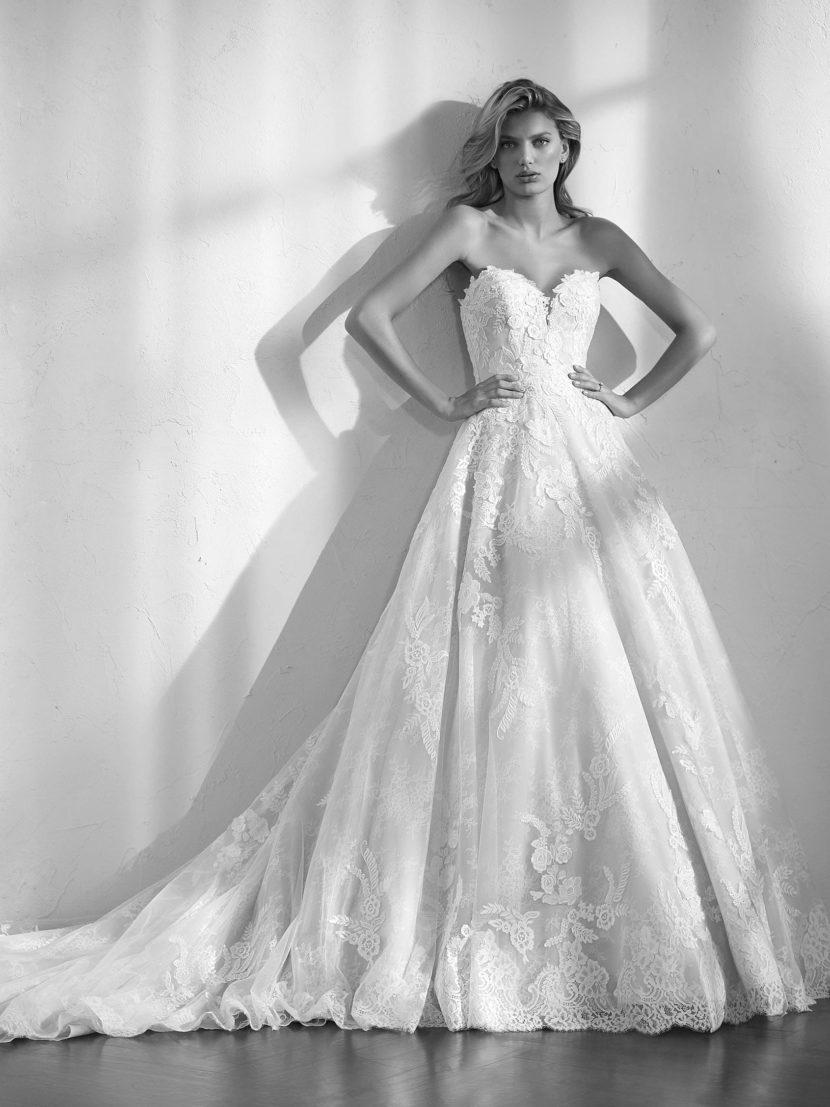 Открытое свадебное платье с многослойной юбкой и кружевным декором.