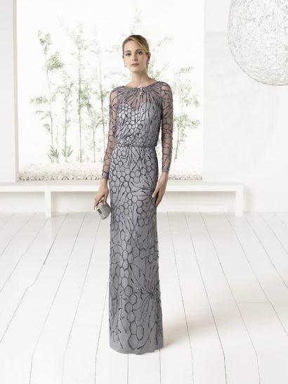 Светло-серый оттенок и прямой силуэт – элегантные черты вечернего платья с юбкой длиной в пол. Закрытый лиф с округлым вырезом дополнен сдержанными длинными рукавами. Контрастом к нему выступает глубокий V-образный вырез на спинке платья.  По всей длине платье покрыто прозрачной тканью, служащей основой для романтичной мерцающей вышивки с крупным рисунком.
