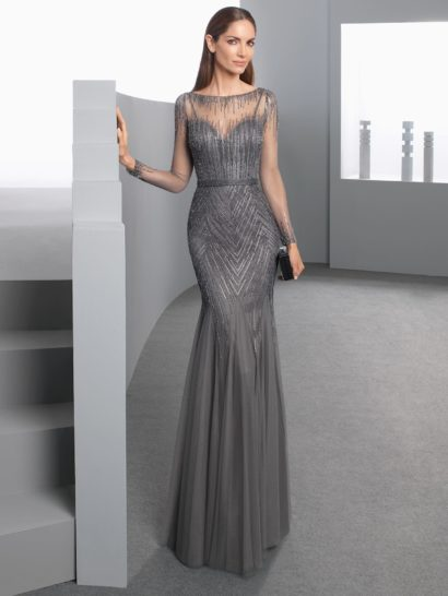Великолепие необычного серого оттенка вечернего платья прекрасно сочетается с женственным прямым кроем. Декольте в форме «сердечка» дополнено прозрачной вставкой с отделкой вышивкой. Вышивка покрывает и верх подола юбки длиной в пол. Сделать акцент в силуэте помогает изящный пояс на естественной линии талии.
