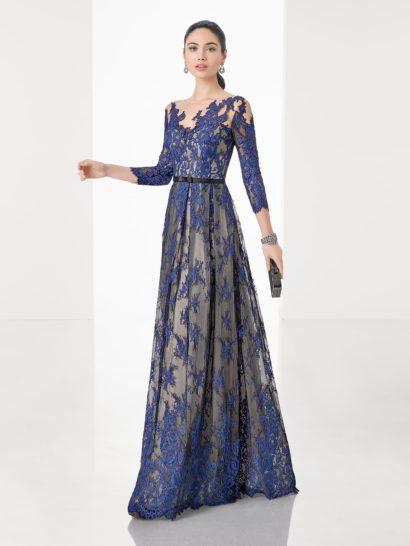 Элегантное вечернее платье А-силуэта впечатляет деликатной комбинацией бежевого и синего оттенков. Фигурный лиф дополнен длинным рукавом из прозрачной ткани с аппликациями. Спинка открыта не менее выразительным вырезом. На талии – узкий пояс черного цвета. Юбка на бежевой подкладке спускается до пола пышными вертикальными складками.