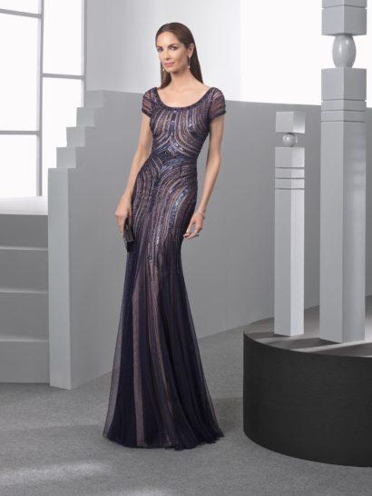 Стильная комбинация темно-серого и бежевого отличает облегающее вечернее платье прямого кроя. Теплый оттенок подкладки, полускрытый темным полупрозрачным верхом, усиливает притягательный характер силуэта. Закрытый верх с коротким рукавом декорирован блестящей вышивкой, такой же декор покрывает и верхнюю часть подола.