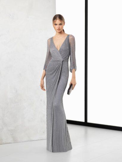 Серое вечернее платье прямого кроя – воплощенная женственность. Облегающий крой с драпировками и V-образным декольте прекрасно подчеркивает фигуру. Закрытая спинка и длинный полупрозрачный рукав обеспечивают образу сдержанность. Деликатный блеск ткани гарантирует вечернему платью максимально торжественный, роскошный вид.