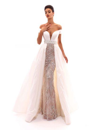 Белое вечернее платье моментально покоряет двойной юбкой. Нижняя очерчивает силуэт и наполняет образ торжественностью благодаря сияющей серебристой вышивке, а верхняя придает платью воздушную пышность. На талии – широкий пояс с бисерным декором. Лиф «сердечком» с глубоким декольте прекрасно создает акцент в силуэте.