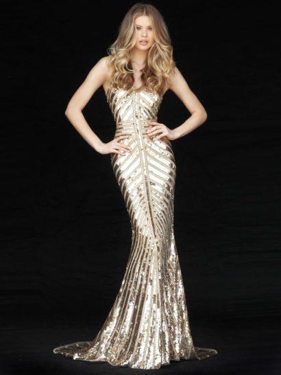 Эффектное золотистое вечернее платье позволит произвести яркое впечатление на окружающих. Широкие линии сверкающего декора из пайеток прекрасно акцентируют линии, созданные облегающим кроем «русалка». Открытые лиф и спинка обрамлены бретельками-спагетти. От уровня коленей сзади легкими волнами спускается небольшой шлейф.