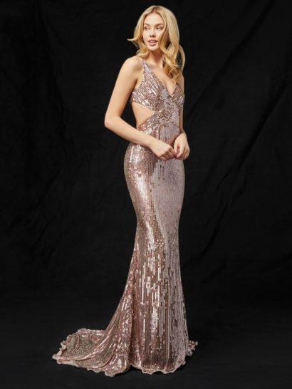 Актуальный оттенок розового золота наполняется роскошью в сиянии пайеток, покрывающих вечернее платье по всей длине. Небольшой вырез на спинке придает прямому силуэту ноты соблазнительности. Изящный лиф на тонких бретелях гармонично поддерживает заданное настроение. Торжественный шлейф делает выразительное платье еще привлекательнее.