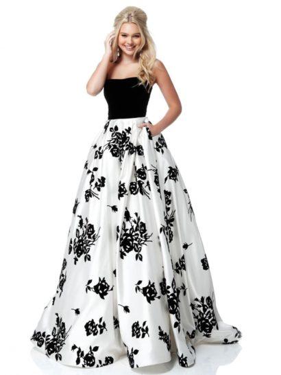 Эффектное вечернее платье пышного силуэта впечатляет контрастами. Юбка длиной в пол покрыта крупным черным узором по белой ткани. Скрытые карманы придают оригинальность роскошному подолу.  Открытый корсет с деликатной линией лифа выполнен из черной ткани, гармонично сочетающейся с цветочным рисунком на юбке.