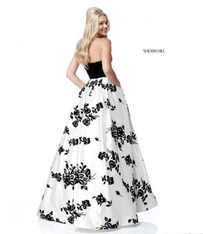 Пышное вечернее платье с черным верхом и белой юбкой с черным узором.