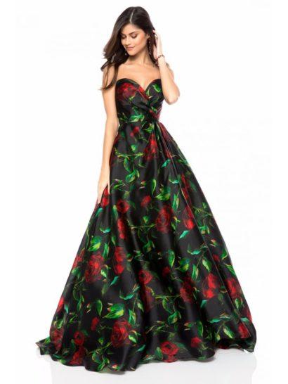 Великолепное вечернее платье создано из оригинальной черной ткани с крупным цветочным рисунком в красно-зеленых тонах.  Открытый лиф с глубоким вырезом «сердечком» подчеркнут элегантными драпировками ткани. Юбку длиной в пол украшают чарующие вертикальные складки, наполняющие образ романтичной красотой при каждом движении.