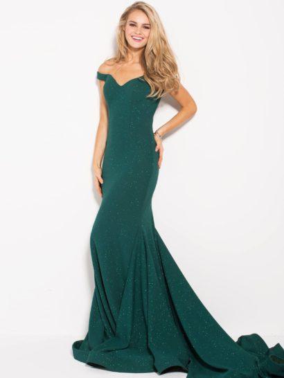 Изумрудное вечернее платье прекрасно подчеркнет фигуру обладательницы. Спущенные с плеч бретели притягивают взгляд к женственному декольте, обнажающему плечи. Эффектную юбку «русалка» украшает шлейф средней длины, спускающийся великолепными вертикальными волнами. Легкий блеск люрекса служит прекрасным украшением образа.