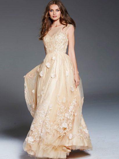 Роскошное свадебное платье теплого пудрового оттенка очаровывает своим романтичным характером. Объемная отделка многослойной юбки, выполненная в виде цветочных бутонов, создает особое настроение. Поддержать его помогает деликатная вышивка бисером. Лиф в форме «сердечка» дополнен полупрозрачной вставкой в тон платью.