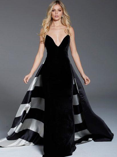 Драматичное вечернее платье очерчивает силуэт облегающей юбкой в пол. Наполнить наряд торжественностью помогает пышная верхняя юбка с отделкой широкими белыми полосами по всей длине подола. Женственные очертания глубокого декольте обрамлены узкими бретелями, симметрично располагающимися на плечах. Спинка вечернего платья открыта.