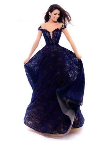 Необычное вечернее платье, наполненное торжественностью. Пышная юбка длиной в пол по всей длине покрыта темно-синим кружевом, подчеркнутым бежевой подкладкой. Драматичный V-образный вырез фигурного лифа дополнен узкими кружевными бретелями, спущенными с плеч. Область декольте дополняет полупрозрачная вставка в тон кожи.