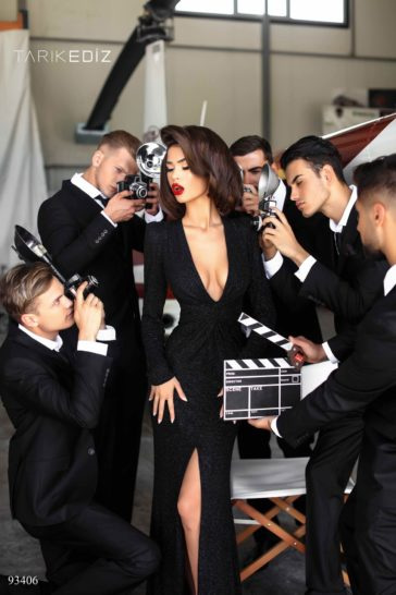 Черное вечернее платье с длинным рукавом и высоким разрезом по подолу.