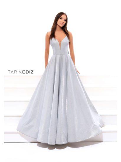 Впечатляющее вечернее платье создано из плотной серебристой ткани с роскошным глянцем. Соблазнительный лиф с вырезом почти до талии дополнен узкими бретелями. На спинке они обрамляют глубокое округлое декольте. Под ним располагается пышный кокетливый бант с широкой лентой, спускающейся вниз по подолу. Пышная юбка в пол наполняет образ особенным настроением.