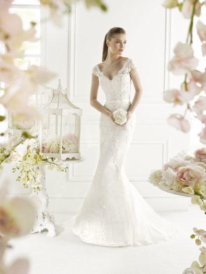 Утонченные линии силуэта «русалка» в комбинации с романтичным кружевом делают свадебное платье безупречным выбором для нежной, мечтательной невесты.  Изящный лиф «сердечком» дополняет тонкая ткань, создающая короткие рукава с фигурным краем.  Она обрамляет и более выразительное V-образное декольте на спинке платья.  Завершением образа служит шлейф, спускающийся от уровня коленей.