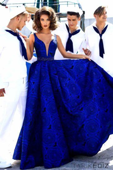 Синее вечернее платье пышного кроя с глубоким вырезом декольте.
