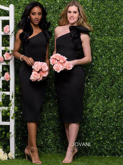 Элегантное вечернее платье черного цвета с облегающей юбкой, спускающейся чуть ниже уровня колена. Вырез через одно плечо стильно дополнен объемной оборкой. Спинка также открыта асимметричным вырезом. Лаконичность в отделке становится главным украшением вечернего образа.