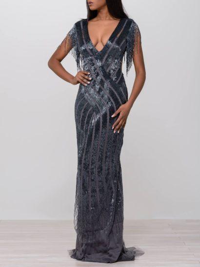 Полностью покрытое бисером вечернее платье темного серебристого оттенка притягивает внимание облегающим силуэтом. Драматизм образу обеспечивают эффектный шлейф, глубокое V-образное декольте и открытая спинка. Кроме того, верх платья дополнен бахромой на рукавах.