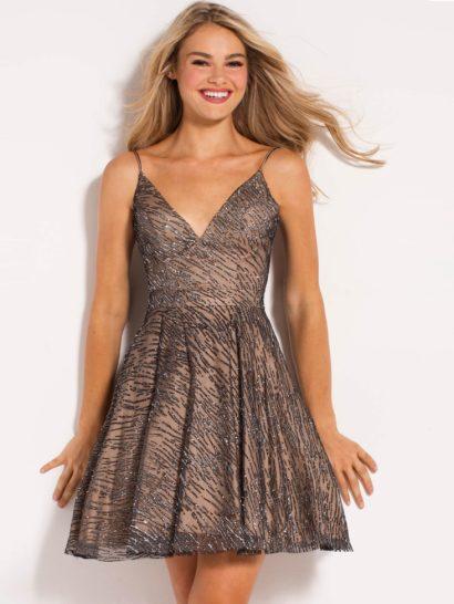 Выпускное платье с бежевой подкладкой, полностью покрытой полупрозрачной тканью с серебристой отделкой. Облегающий верх сочетается с объемной юбкой длиной чуть выше колена. Ее украшают вертикальные складки и скрытые карманы. Лиф без рукавов очерчивает декольте V-образным вырезом на тонких бретелях, симметрично расположенных на плечах.