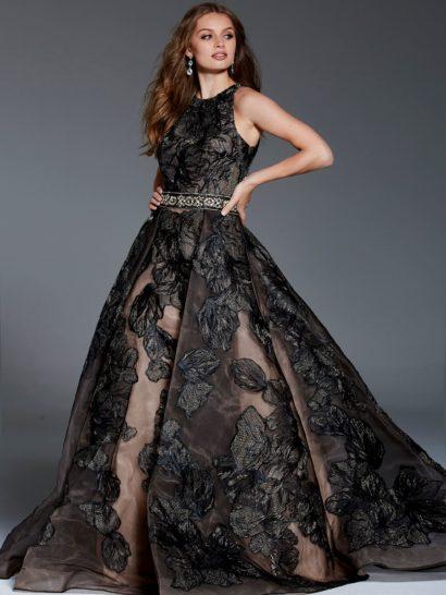 Бальное платье черного цвета с бежевой подкладкой отличается высоким вырезом и отделкой на талии. Это классический торжественный наряд, подкладка которого прекрасно оттеняет драматичный цветочный узор на тонкой черной ткани. Чарующий А-силуэт подчеркнут вертикальными складками на юбке. Элегантный лиф красиво сочетается с открытой спинкой. Вечернее платье будет идеально смотреться на любой фигуре и подойдет для самых торжественных случаев.