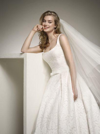 Кружевное свадебное платье с открытым лифом и элегантным шлейфом.