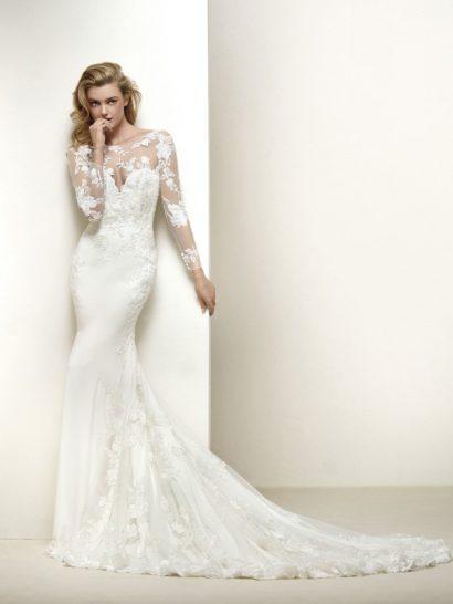 Изысканная элегантность облегающего силуэта в свадебном платье прекрасно оттенена кружевной отделкой по всей длине. Головокружительное декольте дополнено прозрачной вставкой, обеспечивающей длинные рукава и изящный V-образный вырез на спинке. Деликатные вертикальные складки ткани прекрасно смотрятся на небольшом шлейфе из нескольких слоев ткани.