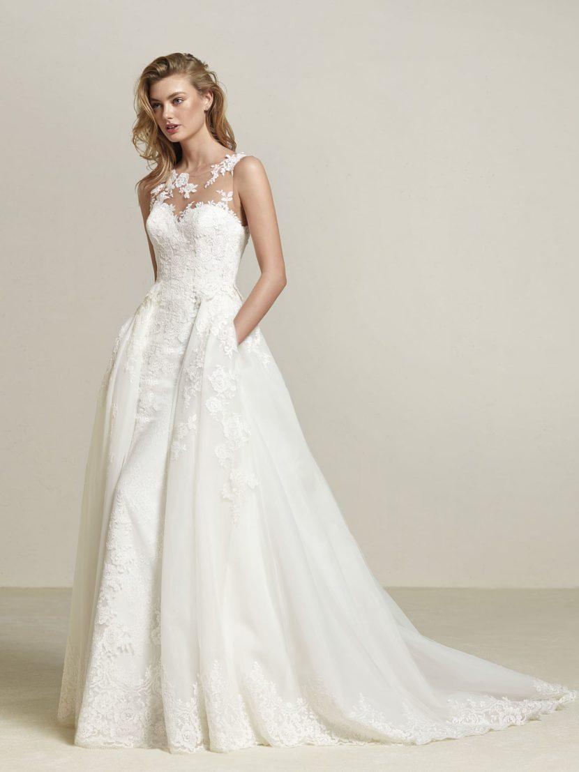 Свадебное платье с кружевным декором и съемной верхней юбкой.